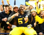 Sophomore Frank Clark celebrates with fans as Michigan wins 12-10 against Michigan State (Credit: Tommy Alexander / MJ)
