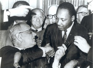 President Lyndon Johnson shakes hands with the Reverend Martin Luther King, Jr., after handing him one of the pens used in signing the Civil Rights Act of July 2, 1964 at the White House in Washington.  (Photo courtesy of U.S. Embassy New Delhi)