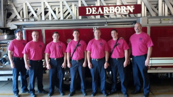 From left to right, Tim Mick, Joey Thorington, Andy Haid, Steve Buchholtz, Ryan Walsh, Jeff Lentz, and Jamie Jent of the Dearborn Fire Department wear pink T-shirts for breast cancer awareness. (Credit Photo submitted by Joey Thorington on Dearborn Patch)