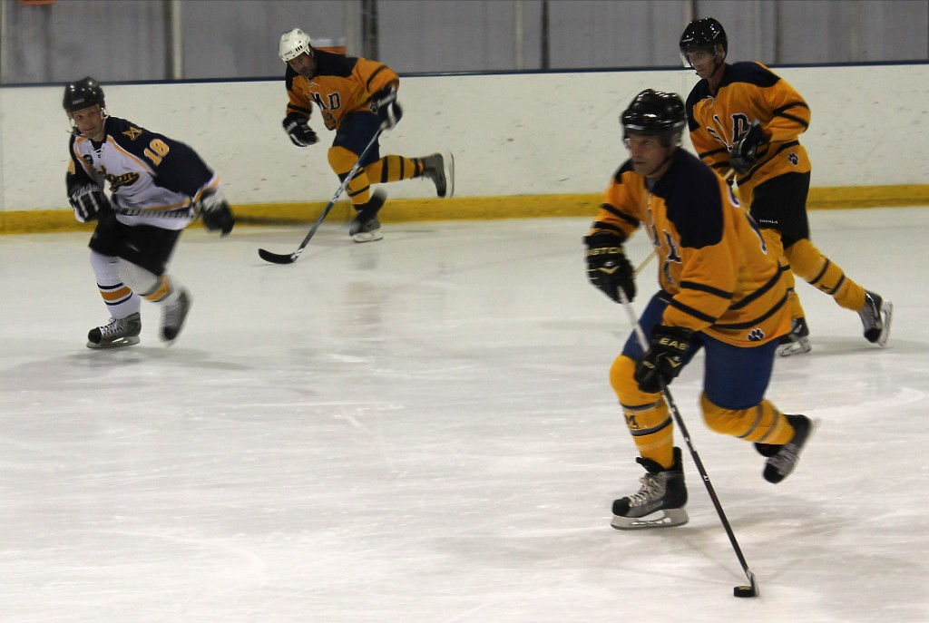 Team Gold moves the puck down the ice during UM-Dearborn's annual alumni hockey game. (Tyesha Vinson/MJ)