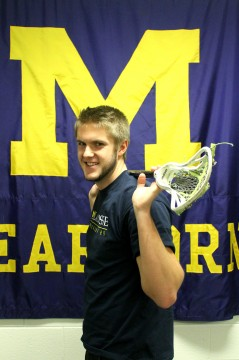 Matt Rosteck poses in front of the UM-Dearborn banner inside the Fieldhouse's conference room. (Brianna Frisch/MJ)