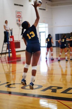 Senior Nia Martin serves while playing volleyball for the UM-Dearborn Lady Wolverines. Photo courtesy of Nia Martin.