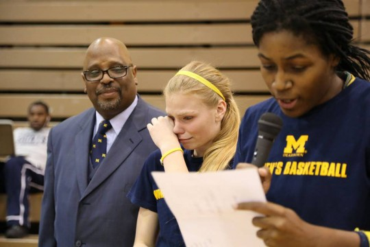 Lady Wolverines head coach Dymetrius Ware looks on as Jalissa Williams reads a speech during Senior Night. Williams led the team in WHAC honors, while Ware has been busy assembling next year's team. (Photo courtesy of University of Michigan-Dearborn Lady Wolverines Basketball Team Facebook page).