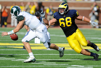 Mike Martin chases then-Michigan State quarterback Kirk Cousins during the Michigan-Michigan State rivalry. (Photo courtesy of AnnArbor.com).