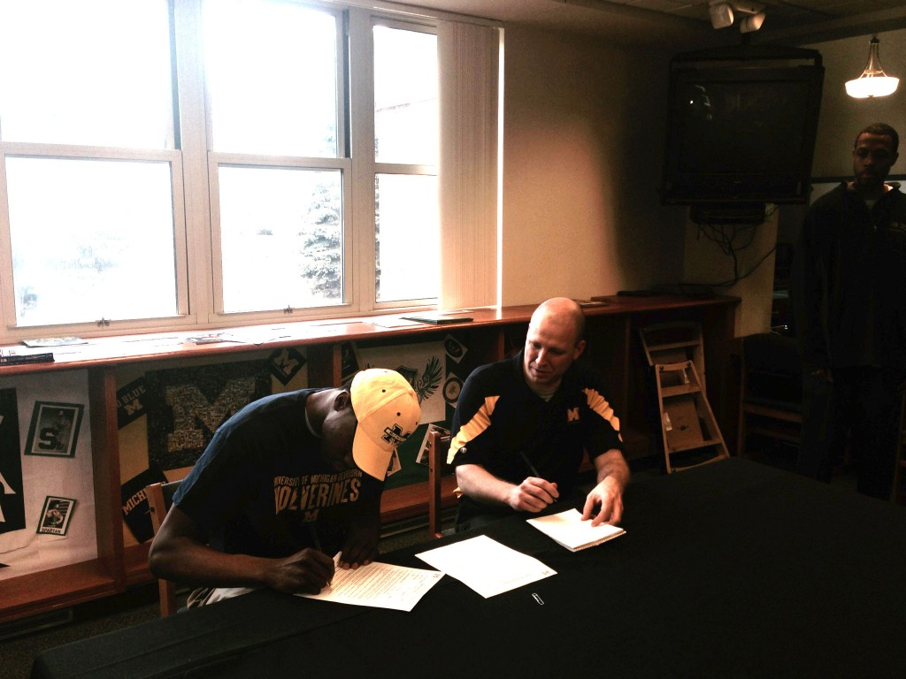 Ferndale University High School forward/center Jason Penn signs his Letter of Intent to play for the Wolverines. (Photo courtesy of John Mackson/UM-Dearborn men's basketball).
