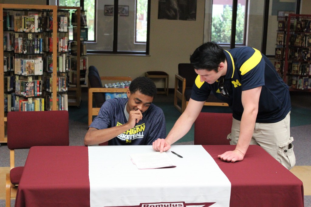 UM-Dearborn coach Taylor Langley looks over paperwork with Deonte Bell before inking the Romulus point guard to a Letter of Intent. Bell committed to the Wolverines on June 3, 2014 after a campus visit and signed 9 days later. (Ricky Lindsay/MJ)