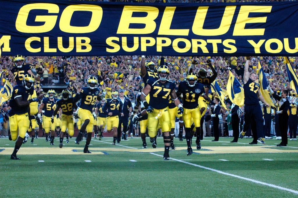 The Michigan Wolverines touch the Go Blue banner before 2013's matchup with Notre Dame. (Amanda Gosline/MJ).