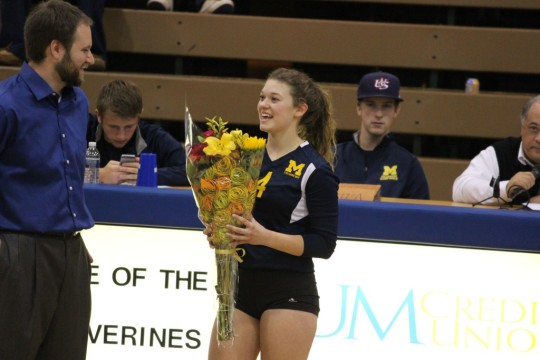 Molly Hilsabeck receives flowers from UM-Dearborn volleyball coach Eric Stark. (Ricky Lindsay/MJ)