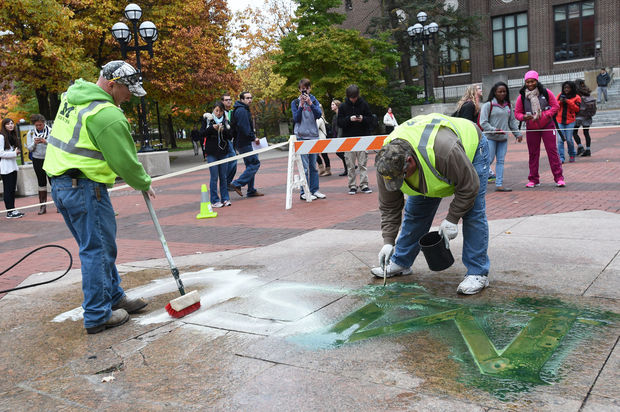"""Cleaning up the vandalized """"M"""" on The Diag in Ann Arbor"""