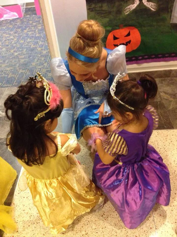 Megan McDonald dressed up as Cinderella while she sits with two other