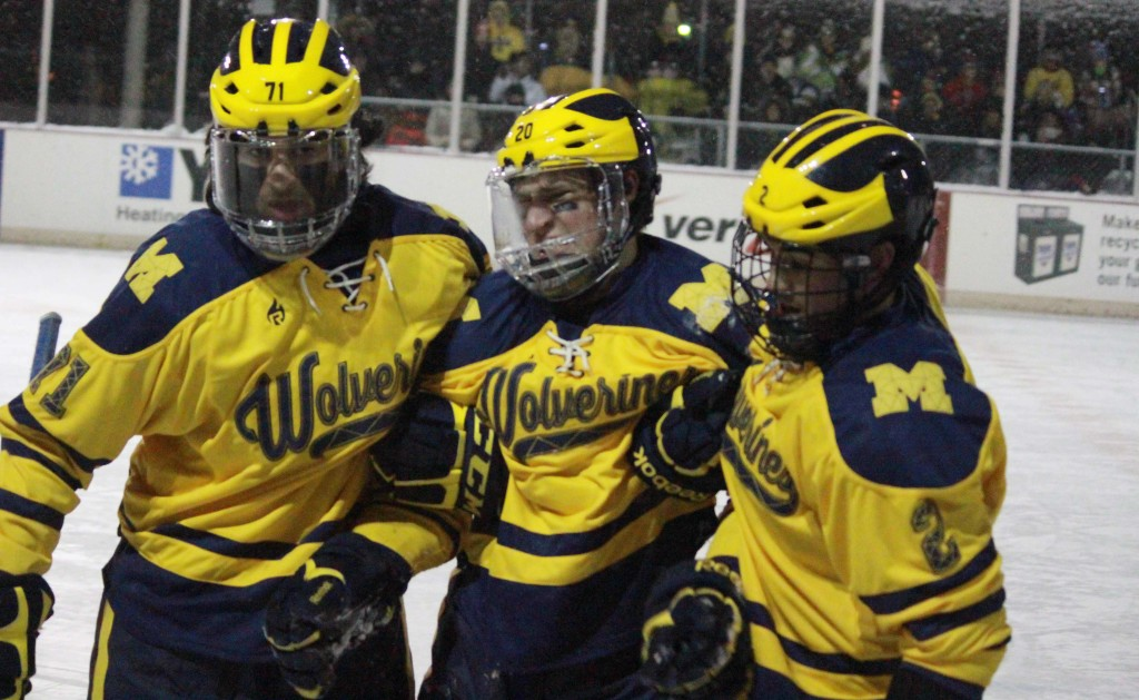 Jeff McFarland (center) is carried off the ice by teammates after suffering an injury against Oakland in UM-Dearborn's outdoor game on Jan. 4, 2015. McFarland has not played since with an injury. (Ricky Lindsay/MJ)